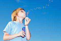 Junge mit Seifenluftblasen gegen einen Himmel Lizenzfreie Stockbilder