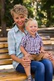 Junge mit seiner Mutter, die auf der Bank sitzt Lizenzfreies Stockfoto