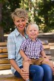 Junge mit seiner Mutter, die auf der Bank sitzt Stockfotos