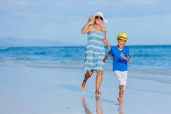 Junge mit seiner Mutter am Strand stockfotografie