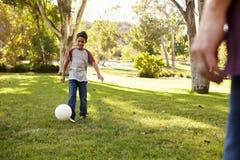 Junge mit sieben Jährigen, der Fußball in einem Park mit Vati spielt lizenzfreie stockbilder