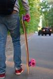 Junge mit Skateboard auf der Straße Stockfotos