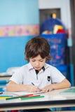 Junge mit Skizze sperrt Zeichnung im Kindergarten ein Lizenzfreies Stockbild