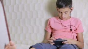 Junge mit Smartphone und Kopfhörern hörend Musik oder Spiel zu Hause spielend stock video