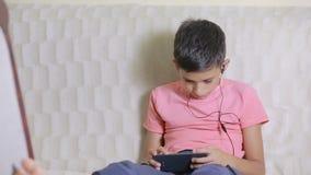 Junge mit Smartphone und Kopfhörern hörend Musik oder Spiel zu Hause spielend stock video footage