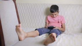 Junge mit Smartphone und Kopfhörern hörend Musik oder Spiel zu Hause spielend stock footage