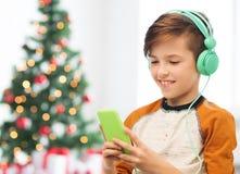 Junge mit Smartphone und Kopfhörern am Weihnachten Lizenzfreies Stockbild