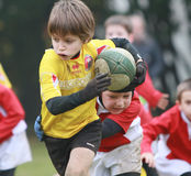 Junge mit Spielrugby der gelben Jacke Lizenzfreies Stockbild