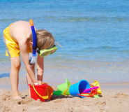 Junge mit Spielwaren auf dem Strand Lizenzfreie Stockbilder