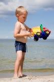 Junge mit Spielzeugauto auf Strand Stockbilder