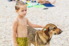 Junge mit Straßenhund Lizenzfreie Stockfotos