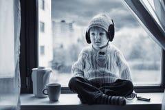 Junge mit trinkendem Tee des Hutes auf dem Fenster Stockfoto