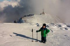 Junge mit Wanderstöcken ein Monument auf dem Berg besuchend Stockbilder