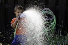 Junge mit Wasserschlauch Stockbild