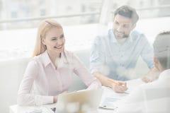 Junge Mitarbeiter, die Gedankenaustausch im modernen Büro haben Stockbilder