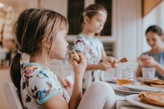 Junge mitfühlende Mutter und ihre zwei kleine Töchter, die Pfannkuchen mit Honig am Frühstück in der gemütlichen Küche essen lizenzfreie stockfotos