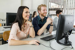 Junge Mitschüler, die einen Monitor und ein Studieren betrachten lizenzfreies stockbild