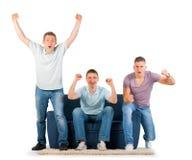 Junge Männer, die auf einem Sofazujubeln sitzen Stockfoto