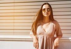 Junge Modefrau bei der Sonnenbrilleaufstellung im Freien über hölzernem BAC Lizenzfreie Stockfotos