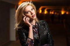 Junge Modefrau in der Lederjacke um Handy ersuchend Lizenzfreie Stockfotografie