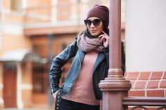 Junge Modefrau in der schwarzen Lederjacke, die auf Geländer sich lehnt stockfoto