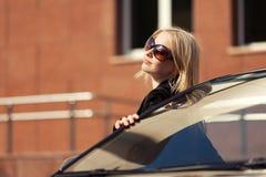 Junge Modefrau in der Sonnenbrille, die ihr Auto bereitsteht Stockfoto