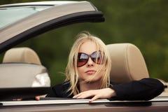 Junge Modefrau in der Sonnenbrille, die konvertierbares Auto fährt Stockfoto