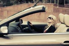 Junge Modefrau in der Sonnenbrille, die konvertierbares Auto fährt Stockbild