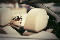 Junge Modefrau in der Sonnenbrille, die konvertierbares Auto fährt Stockfotos