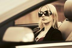 Junge Modefrau in der Sonnenbrille, die konvertierbares Auto fährt Lizenzfreies Stockbild