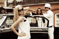 Junge Modefrau in der Sonnenbrille nahe bei Retro- Auto Stockbilder