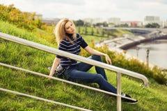 Junge Modefrau, die auf dem Gras im Freien sitzt Stockfoto
