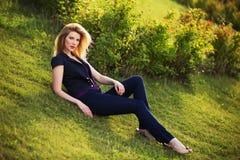 Junge Modefrau, die auf dem Gras im Freien sitzt Lizenzfreie Stockfotografie