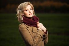 Junge Modefrau, die auf dem Herbstgebiet geht Stockfoto