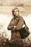 Junge Modefrau, die auf Ufer von See geht Stockbilder