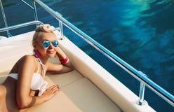 Junge Modefrau, die auf Yacht sich entspannt Stockfotografie