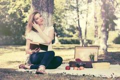 Junge Modefrau, die ein Buch in einem Stadtpark liest Stockbild