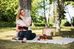 Junge Modefrau, die ein Buch in einem Stadtpark liest Lizenzfreie Stockfotos