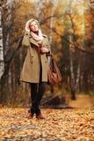 Junge Modefrau, die in Herbstwald geht Stockbild