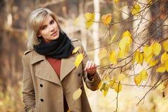 Junge Modefrau, die in Herbstwald geht Lizenzfreies Stockfoto