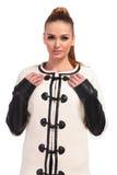Junge Modefrau, die ihre Hände auf der Jacke hält Stockfotografie