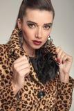 Junge Modefrau, die ihren Kragen zieht Stockfoto