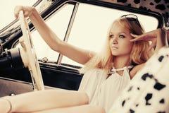 Junge Modefrau, die im Retro- Auto sich entspannt Stockbild