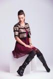 Junge Modefrau, die zusammen ihre Hände sitzt und stillsteht Lizenzfreies Stockfoto