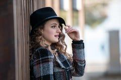 Junge Modefrau im Profilabnutzungshut, der auf einer hölzernen Wand sich lehnt Stockbilder