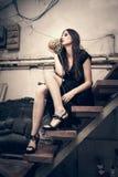 Junge Modefrau im schwarzen Kleid im alten Künstlerstudio sitzen auf s lizenzfreies stockbild