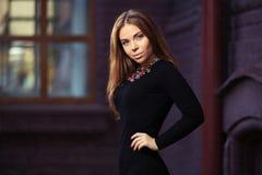 Junge Modefrau im schwarzen Kleid an der Backsteinmauer Stockfotografie