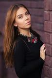 Junge Modefrau im schwarzen Kleid an der Backsteinmauer Lizenzfreie Stockfotografie