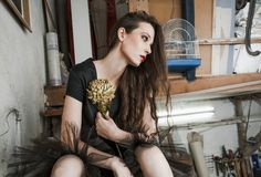 Junge Modefrau im schwarzen Kleid im Künstlerstudio sitzen auf sta lizenzfreies stockfoto