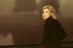 Junge Modefrau im schwarzen Mantel, der auf dem Handlauf im Freien sich lehnt Stockfotografie